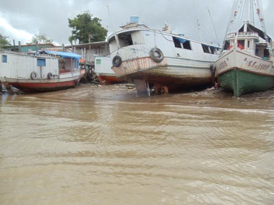 Construtor artesanal  de Abaetetuba, calafetando barco à beira do rio