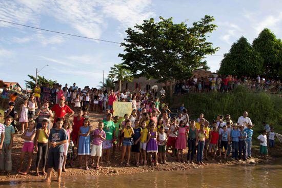 Populares lotam o acanhado porto da cidade, saudando os balseiros com faixas e cânticos.