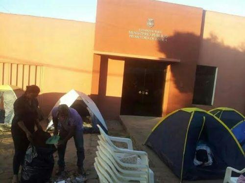 Grevista faz limpeza da calçada onde os manifestantes acampam, em frente ao Ministério Público