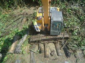 Escavadeira de 27 toneladas assentadas em grandes troncos.