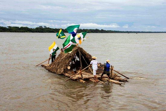 Balsa deixa Imperatriz, desfraldando a bandeira do município, junto com as demais bandeiras de municípios visitados.