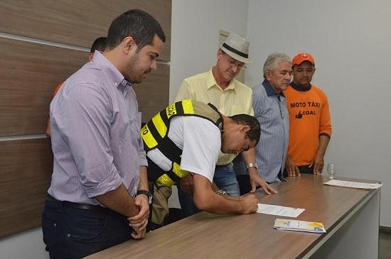Luiz Carlos e mototaxistas no ato de assinatura de decreto