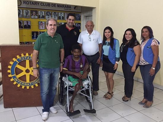 Karam, à esquerda, entrega cadeira de rodas à família de deficiente